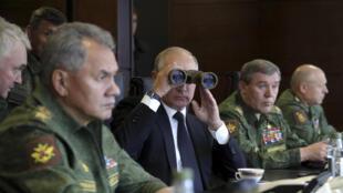 Президент РФ  Владимир Путин и министр обороны Сергей Шойгу наблюдают за ходом учений «Запад-2017» в Ленинградской области 18 сентября 2017.