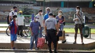 Coronavirus au Pérou: un policier contrôle des passants dans le cadre de la quarantaine imposée pour contrer la maladie, le 26 mars 2020.