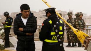 Công an Trung Quốc kiểm tra thẻ căn cước một người Duy Ngô Nhĩ, trong lúc lực lượng an ninh theo dõi các hoạt động trên đường phố ở Kashgar, Tân Cương. Ảnh chụp ngày 24/03/2017.