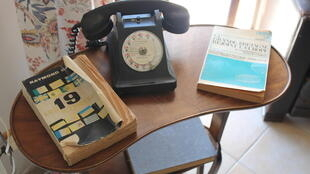 Un viejo teléfono al lado de un anuario telefónico.