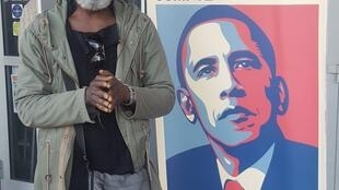 Bordeaux-based artist Pascal Koloko stands in front of a billboard of former US President Barack Obama, at a youth centre on the outskirts of Bordeaux during Black History Month