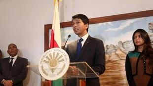 Andry Rajoelina speaks to the press before leaving for the meeting