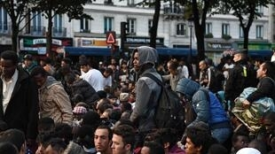 Migrants gather and wait before being evacuated from a makeshift migrant camp set up between the metro stations of Jaures and Stalingrad, in Paris, on September 16, 2016.