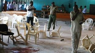 Kenyan police inspect the scene after the attack by gunmen in a Mombasa church