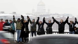 Militantes da oposição enfrentam o frio para fazer corrente humana contra a eleição de Vladimir Putin na presidência.