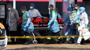 Personal médico se lleva en camilla a un paciente con coronavirus trasladado en tren desde París hasta Quimper, el 5 de abril de 2020 en la estación de esa localidad al oeste de Francia
