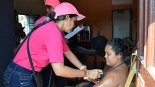 Uma mulher grávida recebe uma aplicação de repelente em Soledad, perto da cidade de Barranquilla, na Colômbia.