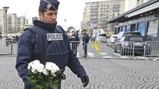 A French police officer places flowers outside the Hyper Cacher kosher supermarket near Porte de Vincennes