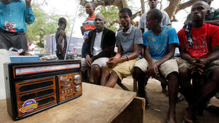 Youth in Liberia gather to listen to President George Weah's coronavirus song on the radio