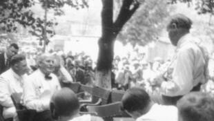Lors du procès, William Jennings Bryan (assis, à gauche) est interrogé par Clarence Darrow (debout, à droite).