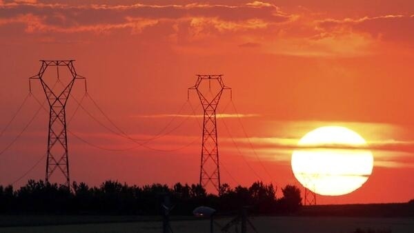 The sun sets behind high-tension electrical power pylons in Poitiers, central France, 5 June 2015