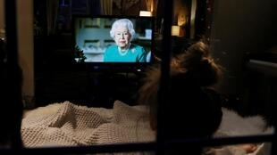 Des habitants de Henton regardent la reine Elizabeth II de Grande-Bretagne lors d'une allocution télévisée le 5 avril 2020.