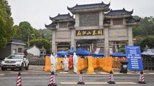 Gente con trajes protectores, como medida preventiva contra la epidemia de COVID-19, en el puesto de control de un acceso del cementerio de Biandanshan, en Wuhan, centro de China, el 31 de marzo de 2020