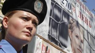 Сотрудница украинской полиции перед плакатом с портретом Юлии Тимошенко на демонстрации 1 мая 2012 г. в Киеве