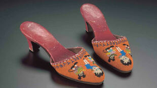 A pair of beaded orange slippers with Betty Boop and Mickey Mouse