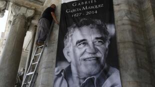 Un trabajador coloca el afiche que anuncia el homenaje a Gabriel García Márquez en la fachada del Palacio de Bellas Artes, ciudad de México.