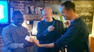 Grand Corps malade, président du jury, remet à Émile-Vitus Tossou le premier prix du concours E-pop devant son fondateur Max Bâle.