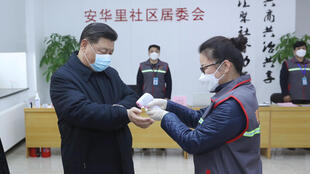 Chinese President Xi Jinping, wearing a face mask has his temperature checked in Beijing