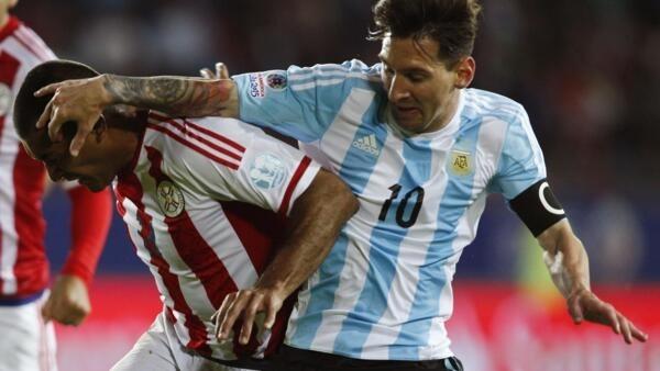 Messi (à direita) disputa bola com paraguaio Paulo da Silva.