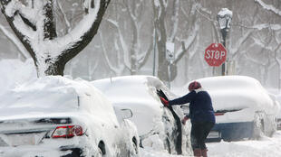 Limpando o carro coberto de neve durante uma tempestade do inverno em Búfalo, New York, EUA, 31 de janeiro de 2019.