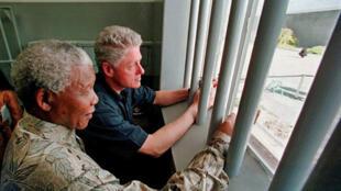 Avec le président américain, Bill Clinton dans la cellule de la prison de Robben Island où Nelson Mandela a passé 18 des 27 années de captivité, mars 1998.