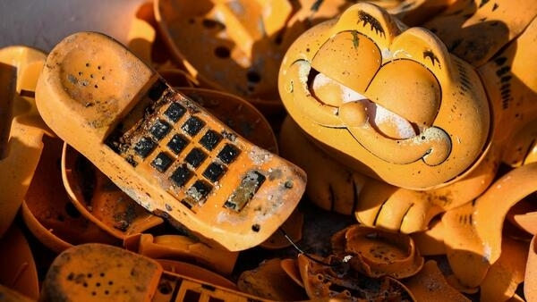 Spare parts of plastic 'Garfield' phones are displayed on the beach in Plouarzel, western France, 28 March 2019