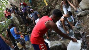 Les Vénézuéliens remplissent des bidons avec l'eau des nombreux ruisseaux au pied de la montagne qui domine Caracas, le 31 mars 2019.