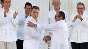 Colombian President Juan Manuel Santos (centre left) and Farc leader Timochenko shake hands after agreeing the peace deal