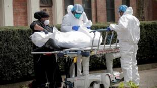 Du personnel soignant évacue le corps d'un malade décédé du coronavirus à New York le 8 avril 2020.