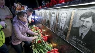 A woman lays flowers at a memorial, dedicated to firefighters and workers who died after the Chernobyl nuclear disaster.