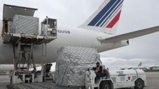 Des eployés de l'aéroport de Roissy déchargent une cargaison de masques d'un avion d'Air France en provenance de Chine, le 29 mars 2020.