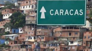 En la vía del aeropuerto internacional de Maiquetía, en Venezuela, un cartel indica la dirección de Caracas, ciudad que podría acoger a Snowden. En el fondo, un barrio marginal en la periferia de la capital venezolana.