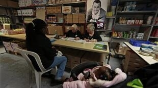 """A woman and her baby wait to be registered in charity food centre """"Les Restos Du Coeur"""""""