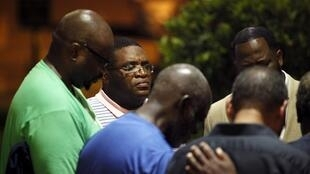 A small prayer circle forms nearby where police are responding to a shooting at the Emanuel AME Church in Charleston, South Carolina June 17, 2015.