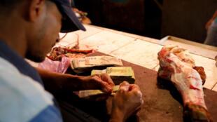 Cả xấp tiền bolivar chỉ mua được một khúc xương. Ảnh chụp tại một hàng thịt ở Maracaibo, Venezuela ngày 26/07/2018.