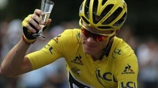 Great Britain's Christopher Froome is enjoys a glass of champagne as he rides during final stage of the Tour de France on July 24, 2016
