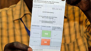 """An electoral official holds up a """"yes"""" vote at a polling centre in Eldoret town."""