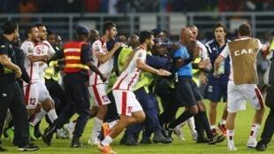 L'arbitre Rajindraparsad Seechurn protégé des joueurs tunisiens par les forces de l'ordre équato-guinéennes.