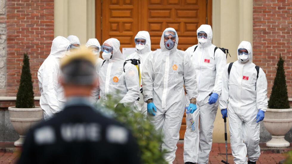 Các quân nhân thuộc Đơn vị Khẩn cấp rời khỏi nhà một người già sau tại Madrid sau khi tiến hành khử trùng để ngừa dịch Covid-19. Ảnh chụp ngày 23/03/2020.
