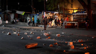 Haitians stand near a barricade made of debris during a protest in Port-au-Prince