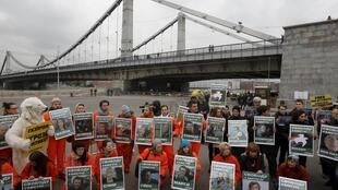 Simpatizantes do Greenpeace exibem durante protesto neste sábado em Moscou, imagens de tripulantes do Arctic Sunrise.