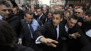 Nicolas Sarkozy walks in the street protected by plain-clothes policemen during a campaign trip in Bayonne, 1 March 2012