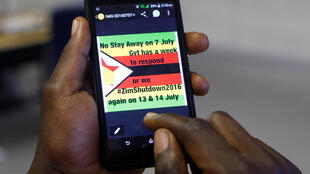 A man checks a message on his mobile phone, in Harare, Zimbabwe, July 7, 2016