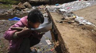 Criança bebendo água em Fuyuan, China