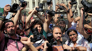 Egyptian journalists hold up their cameras outside the Egyptian Press Syndicate in Cairo to protest against restrictions on press freedom