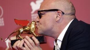 """O diretor italiano Gianfranco Rosi beija o troféu que recebeu em Veneza pelo melhor filme em competição, o documentário """"Sacro Gra""""."""