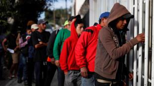 Migrantes latino-americanos fazem fila para ganhar refeição em ginásio esportivo de Tijuana transformado em centro de acolhimento.
