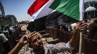 Un manifestant, le drapeau du Soudan à la main, fait le V de la victoire, près du QG de l'armée à Khartoum, le 21 avril 2019.