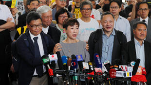 "Pro-democracy activists arrive at the court before hearing a verdict on their involvement in the Occupy Central, also known as ""Umbrella Movement"", in Hong Kong"