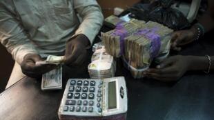 Echange de dollars avec des nairas nigérians, à Lagos (Nigeria).